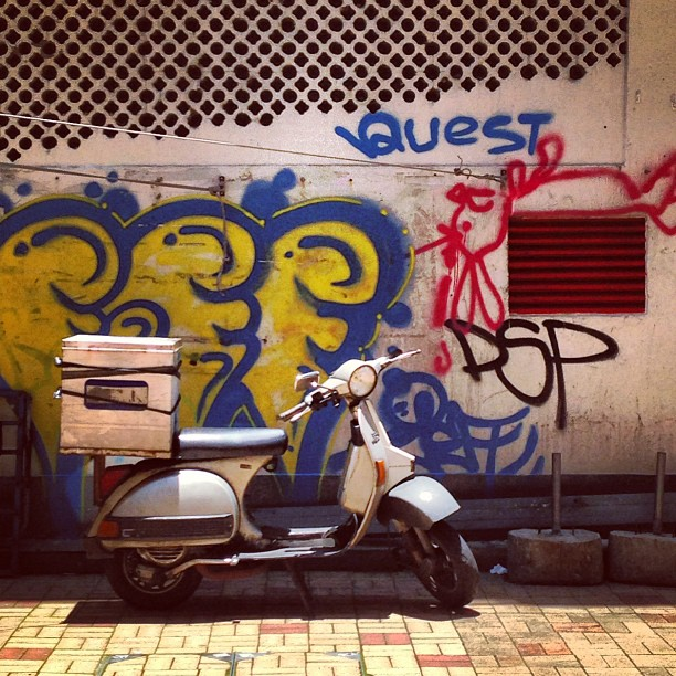 A Delivery Vespa On A Background Of Graffiti