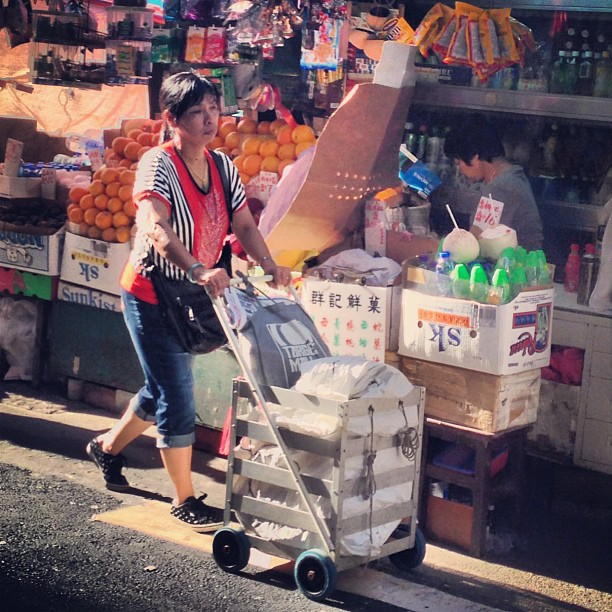 A #lady wheels her #trolly with a #fruit #stall in the background. #hongkong #hk #hkig