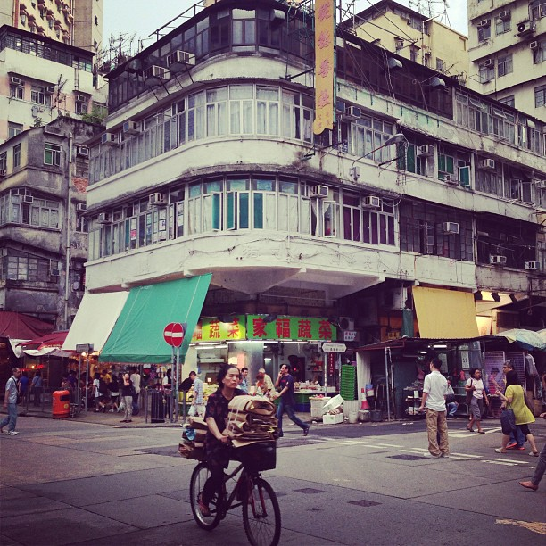 A glimpse of #old #hongkong - a #lady rides a #bicycle past a #tonglau in #ShamShuiPo. #hk #hkig