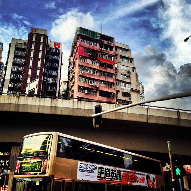 Slice of life - everyday scenes: a #bus passes under a #highway next to a block of #apartments. #hongkong #hk #hkig