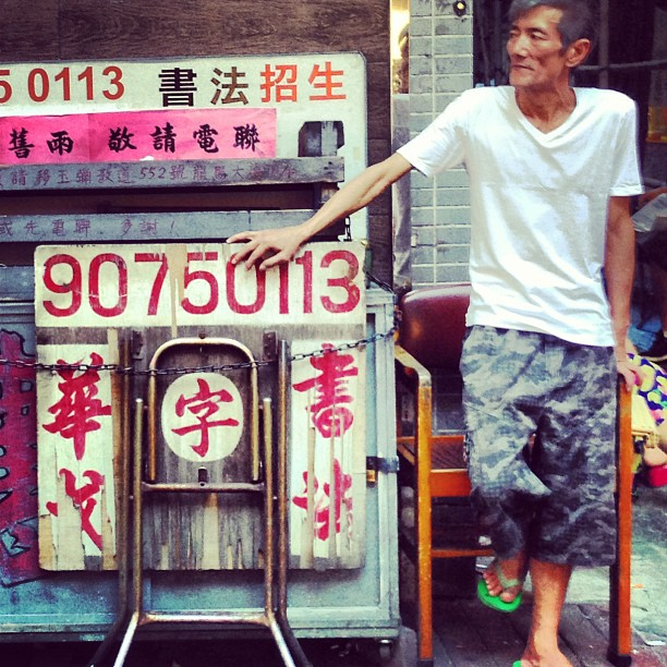 An #old #man leans on a folded #table that advertises #calligraphy lessons. #hongkong #hk #hkig #mongkok