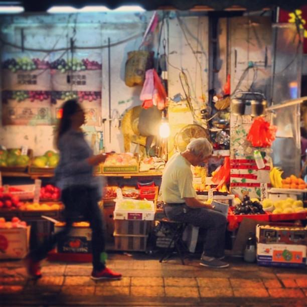 A lady rushes past a #streetcorner #fruit #stall at #night. #hongkong #hk #hkig