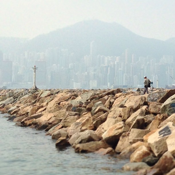 A #man walks along a #breakwater while a #hazy #hongkong #island looms in the background. #hk #hkig