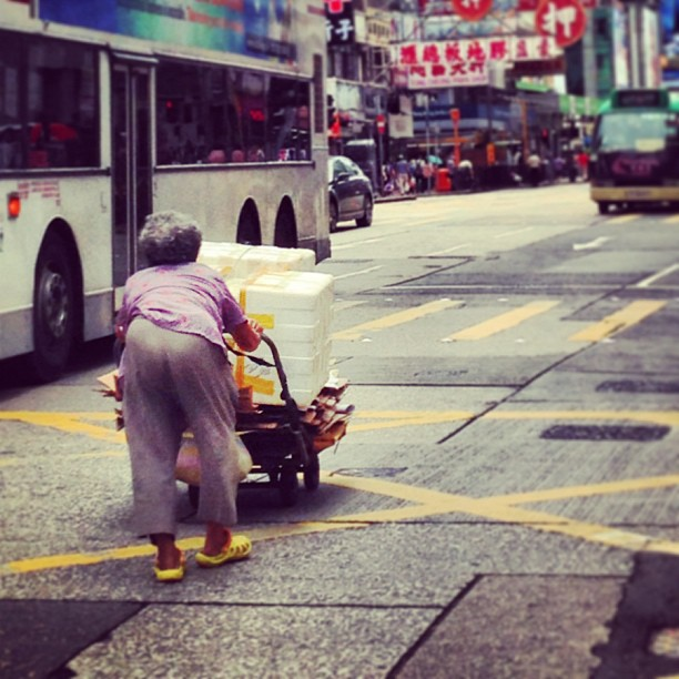 An hunched #old #lady pushes her cart of recyclables along a busy #road. #hongkong #hk #hkig