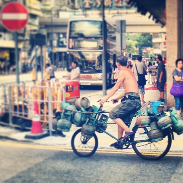 An #old #man on a #bicycle carries a cargo of used #gas tanks to be recycled. #hongkong #hk #hkig