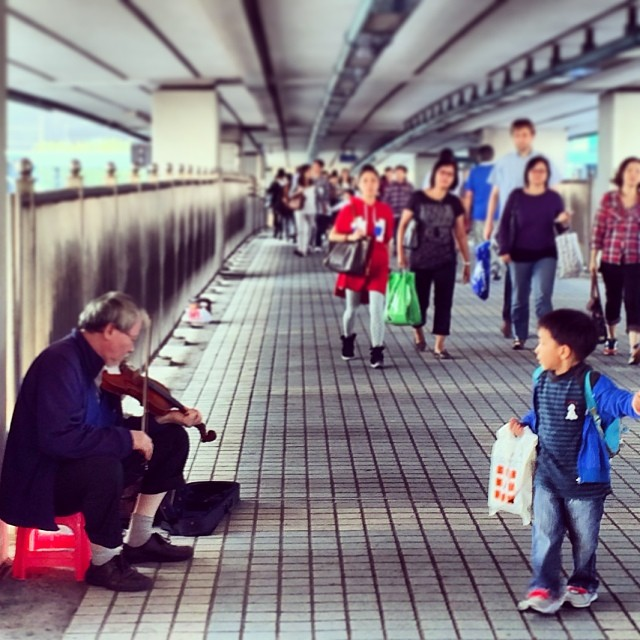A young #boy stops to watch an #old #man play the #violin. #hongkong #hk #hkig #busker