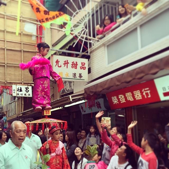 A girl perched on top of an #umbrella at the #piusik #parade at the #cheungchau #bunfestival. #hongkong #hk #hkig