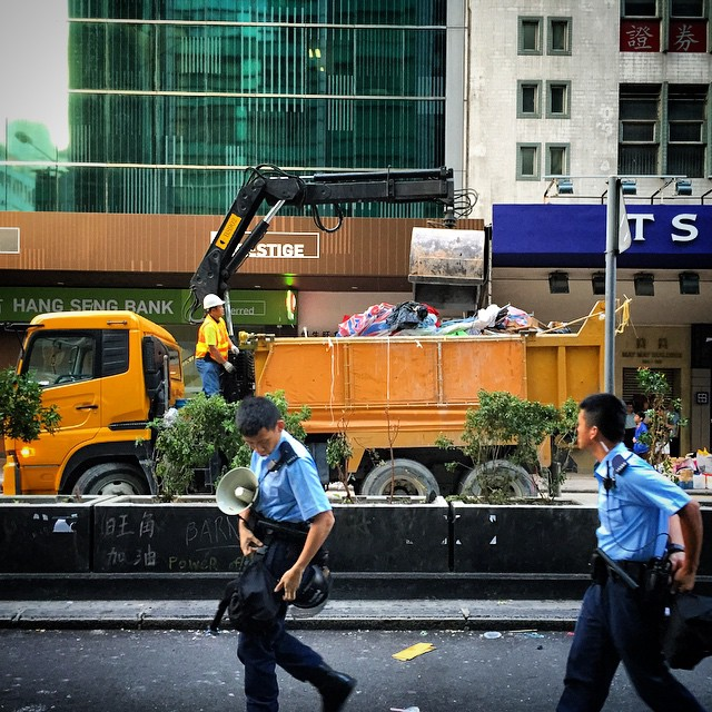 A #truck with attached #crane arm clears tents and debris on #NathanRoad while #police officers stream past. #OccupyHK #Mongkok is being cleared out. #HongKong #hk #hkig #umbrellarevolution