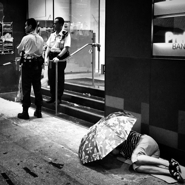 After a long night of protests - an #OccupyHK #protester sleeps under an #umbrella while two #police officers stand nearby. #umbrellarevolution #mono #HongKong #hk #hkig #Mongkok