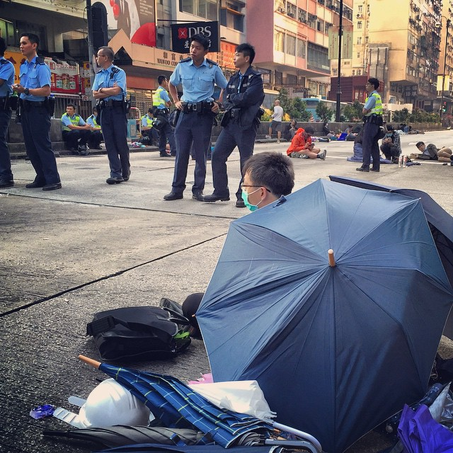 An #OccupyHK #protester shelters behind an #umbrella while #police loiter around. #HongKong #hk #hkig