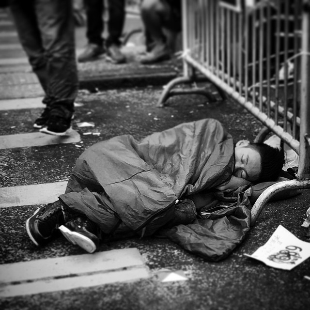 An #OccupyHK #protester sleeps by a #barricade on #NathanRoad in #Mongkok while gawkers and onlookers walk by. #mono #HongKong #hk #hkig