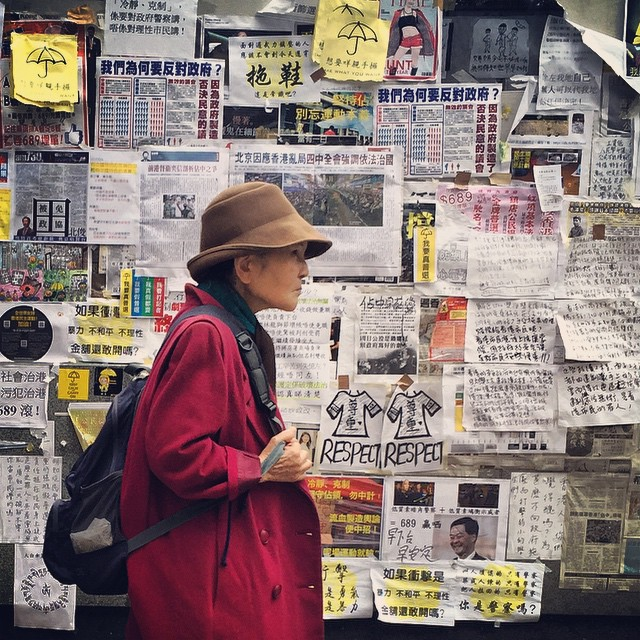 An old #lady walks past a wall filled with #OccupyHK #flyers and #posters in #Mongkok. #HongKong #hk #hkig