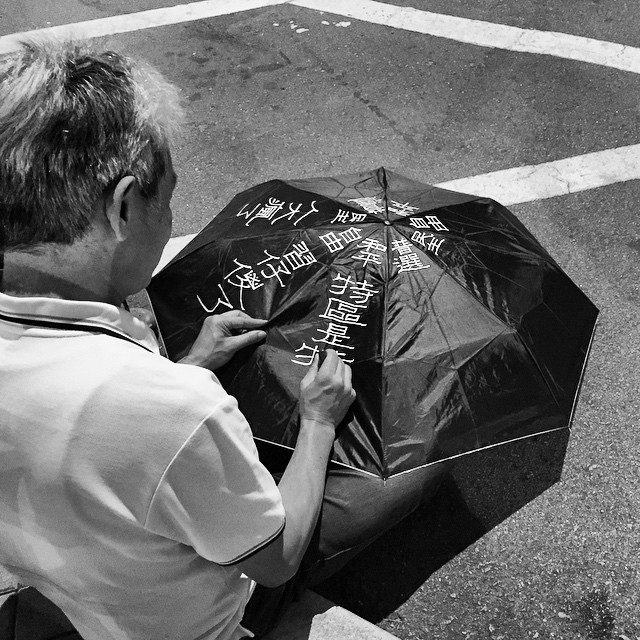 At #OccupyHK in #Admiralty an old man patiently writes protest slogans on an #umbrella using correction fluid. #HongKong #hk #hkig #mono