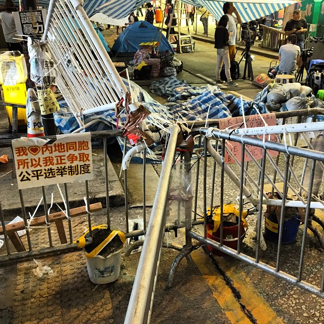 Night 16 of #OccupyHK in #CausewayBay - rumours of #cement being used to reinforce the #barricades have been greatly exaggerated. As you can see from the pic, they've poured cement into buckets and attached it to the #barriers to make them heavier. They haven't actually cemented the barricades to the ground.