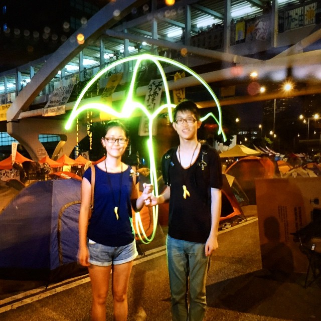 #umbrella of #light at #OccupyHK? No, just more awesome #protest #art at the #umbrellarevolution site in #Admiralty. This is long exposure light drawing. The subject stands still for about 5secs and a person with a flashlight goes behind them and draws the light-umbrella. A flash fires on the first moment to lock in the subjects, the light drawer pops in after the flash and thus doesn't show up (much) in the pic. If you haven't guessed, this is a pic of a pic, taken from the proofing screen. #HongKong #hk #hkig