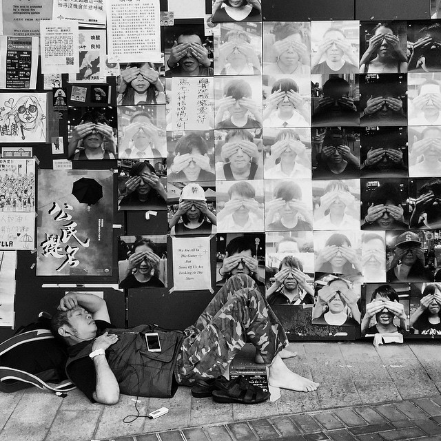 An #OccupyHK protester sleeping on the street, in front of a wall of #posters. #HongKong #hk #hkig