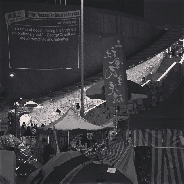 #OccupyHK #Admiralty night scene - the #LennonWall, the #UmbrellaMan (can you spot the him?) and the #AddOilMachine. The Add Oil Machine projects messages submitted at the website on the wall for all to see. #HongKong #hk #hkig #mono