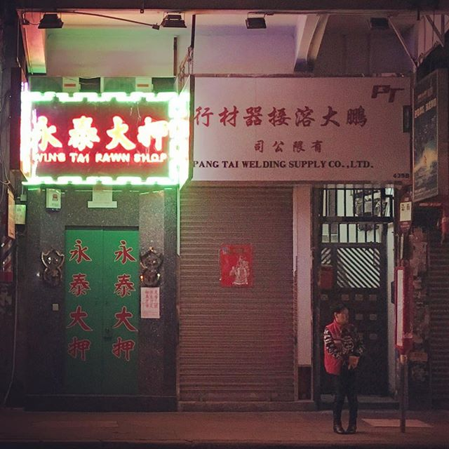 The #neonsign of a #pawnshop lights up the #street where a lone commuter waits at a #busstop. #neon #HongKong #hk #hkig